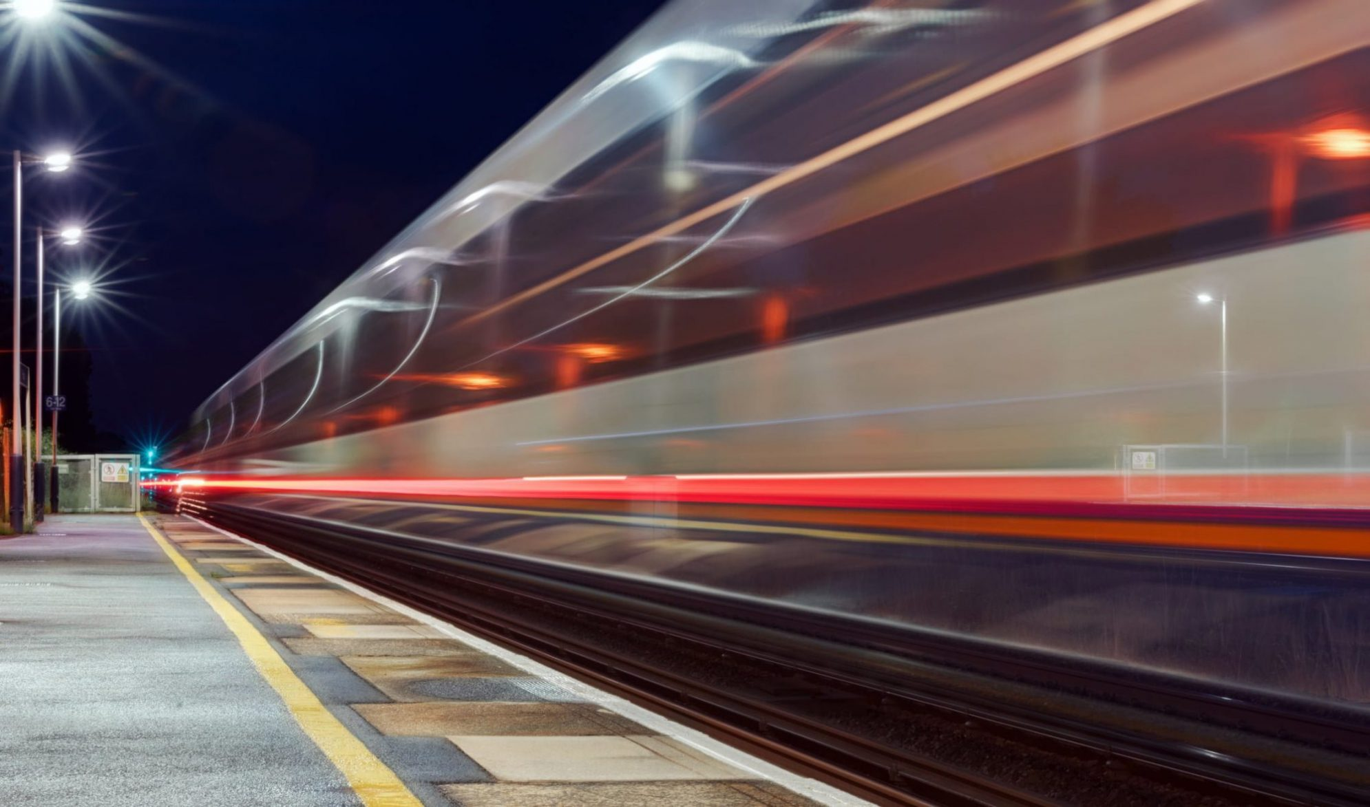 Train passing through a UK station at high speed captured as motion blur